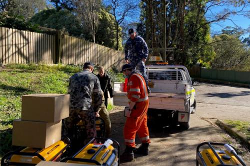 Photo of personnel lifting generators onto the back of a ute